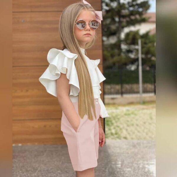 Девочка в пудровых шортах и белой блузке