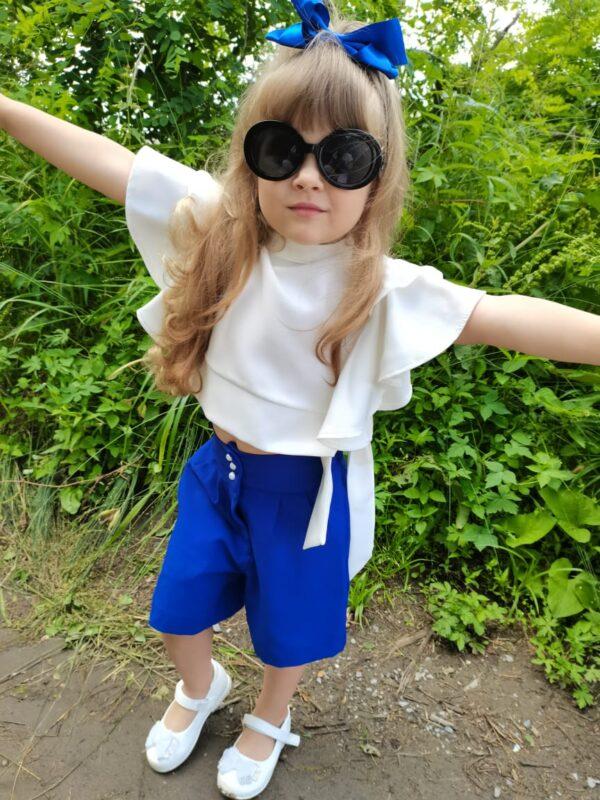 Девочка в синих шортах и белой блузке