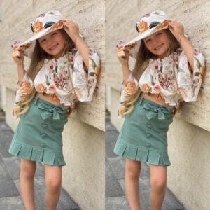 Девочка в блузке с длинным рукавом и юбке