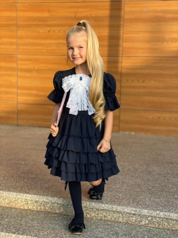 Девочка в школьном платье с бантом впереди