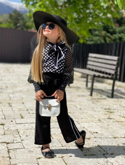 Девочка в брюках и блузке в горошек