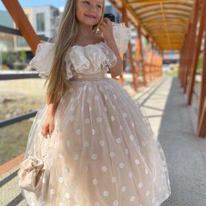 Девочка в бежевом платье с открытыми плечами